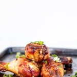 Roasted Chicken leg marinated in soy and burnt caramel marinade with dusting of spring onion slices on a sheet pan