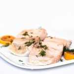 A pair of poached salmon fillet on a plate decorated with slices of orange and bits of dill