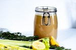 A glass container filled with chicken broth and surrounded by celery, thyme, rosemary and lemon
