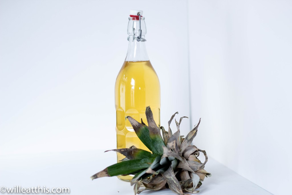 A bottle filled with clear yellow pineapple citron syrup with the crown of the pineapple fruit.
