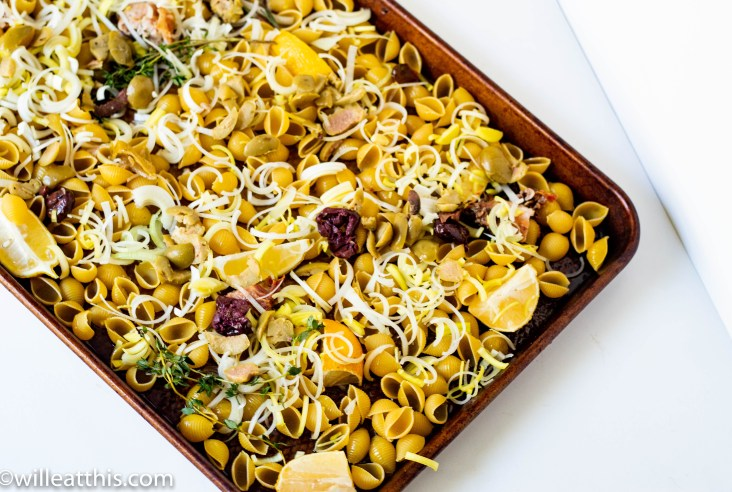A baking tray filled with uncooked pasta with lemon, leeks, olives and herbs.