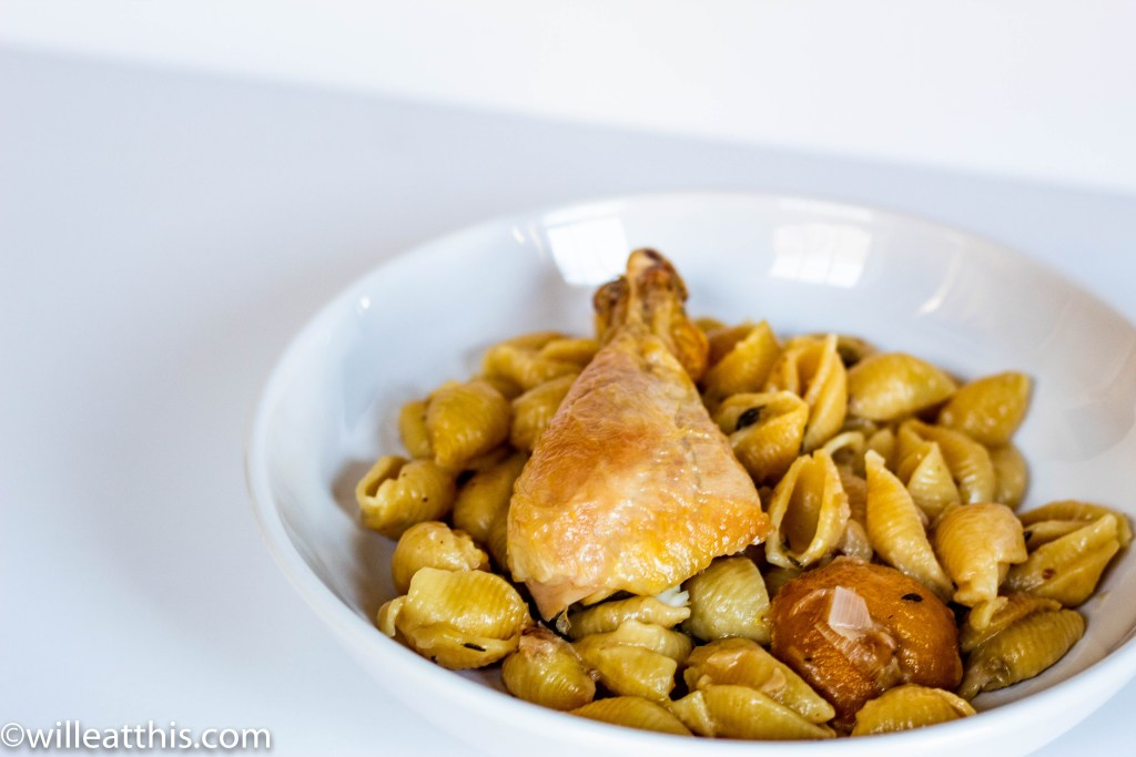 A white plate filled with pasta cooked with leek and lemon. It is topped with roasted chicken drumstick