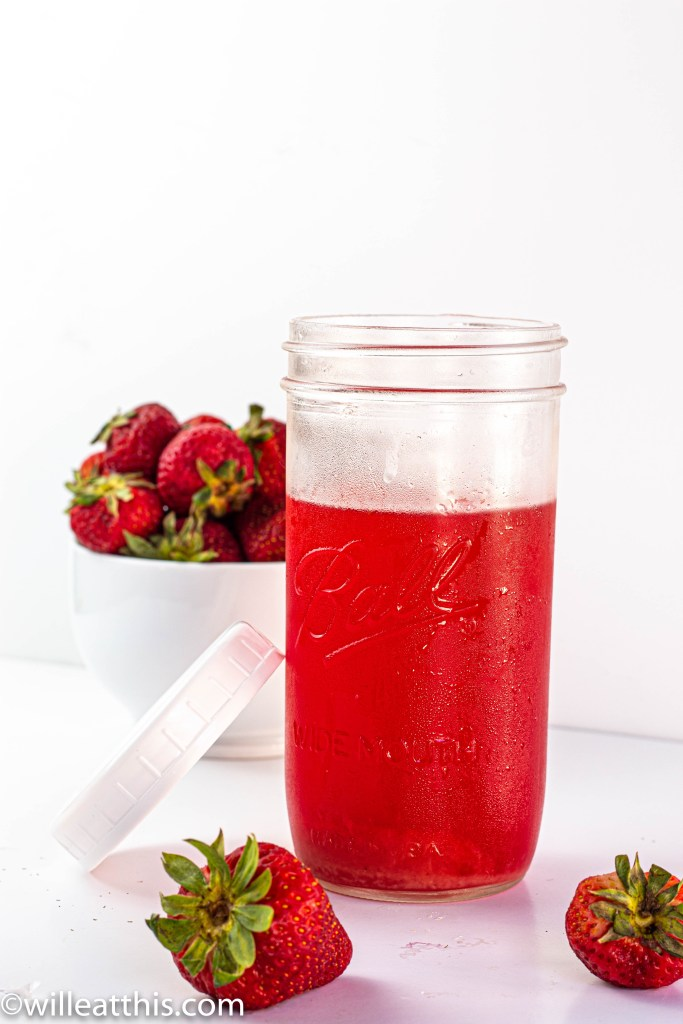 A jar of strawberry and rhubarb cordial with a wide lid resting against the glass jar. There are strawberries in the background.