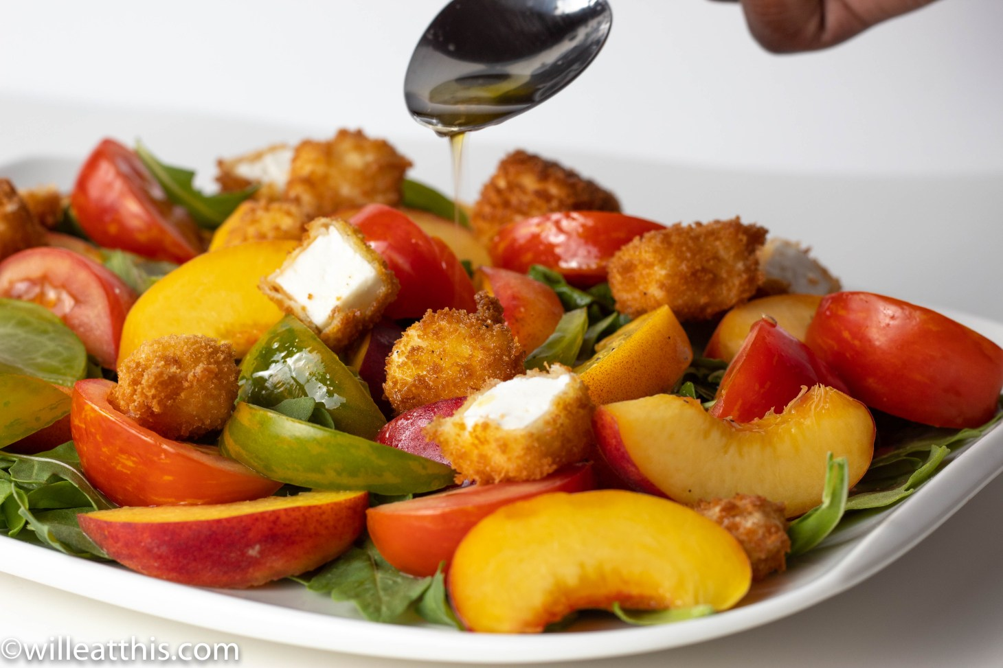 Drizzling oil on a platter of peach tomato salad with feta crouton