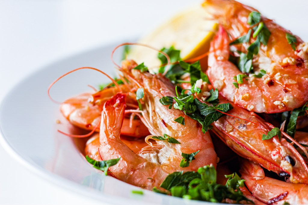 Cooked pink shrimp in lemon butter sauce dusted with chopped parsley leaves heaped in a white bowl.