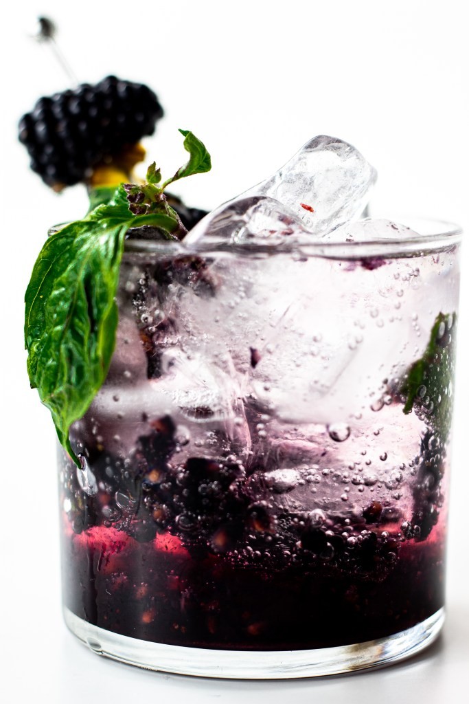 A glass of blackberry jalapeno smash mocktail with ice.