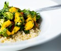mango salad with tomato and avocado served on white quinoa in a white plate