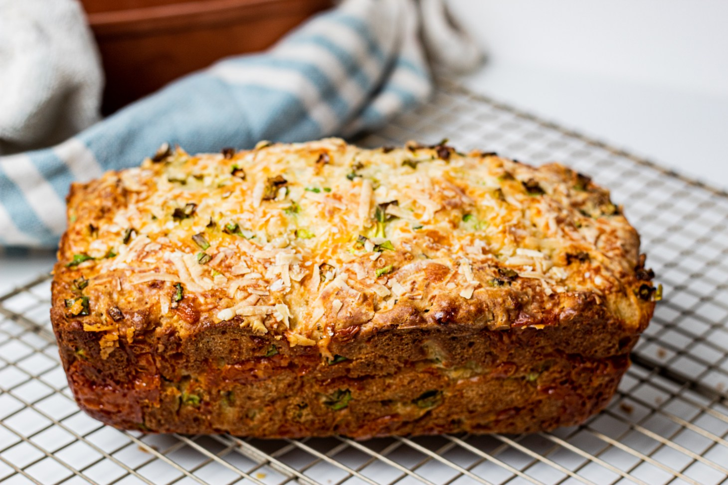 Baked Loaf of Cheddar and Spring Onion bread on a rack