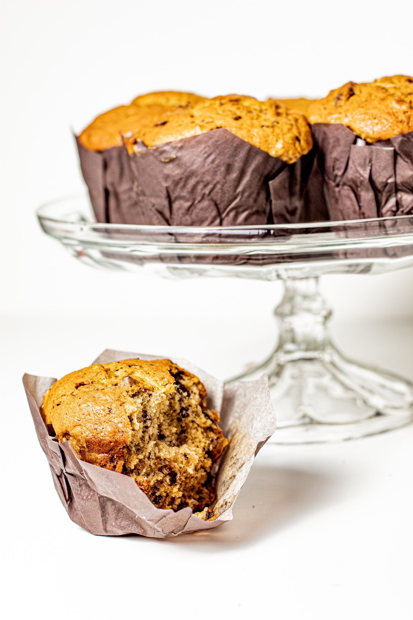 chocolate chip buttermilk banana bread muffin on a cake stand with a single bitten muffin below