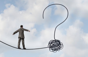 Risk uncertainty and planning a new journey as a businessman walking on a tight rope that getets tangled and shaped as a question mark as a metaphor for confusion at the road ahead as a business concept of finding solutions to change for success.