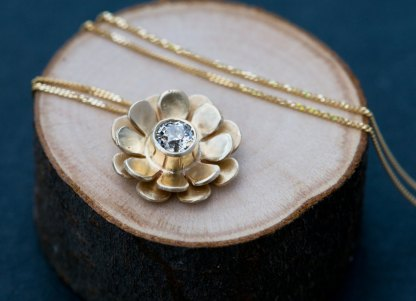gold flower necklace with diamond flower centre