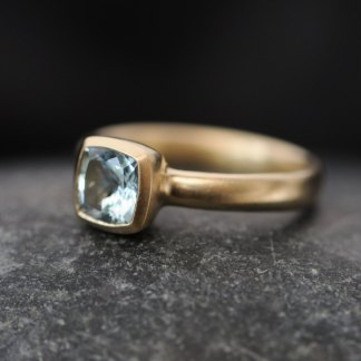 Cushion cut aquamarine stone set in yellow gold ring