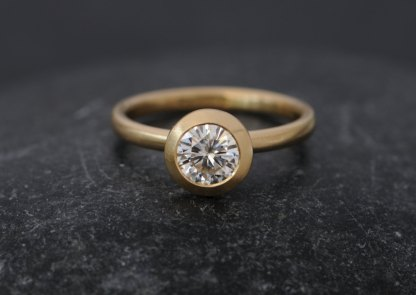 Contemporary solitaire ring featuring Forever Brilliant Moissanite set in 18k gold. By William White