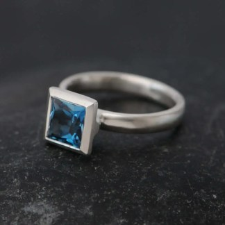 Contemporary square setting princess cut blue topaz in silver ring. By William White
