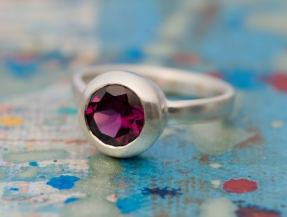 Beautiful deep pink Rhodolite Garnet, set in satin finished sterling silver. A lovely alternative engagement ring. By William White