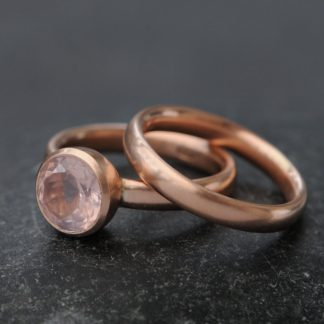 pink rose quartz stone in rose gold engagement ring with matching wedding band
