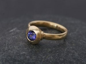 Purple blue tanzanite stone set in yellow gold button ring