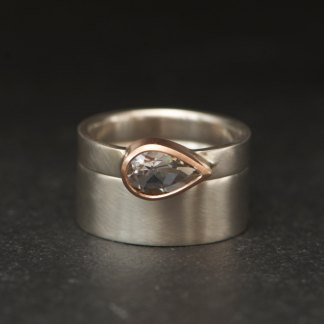 White topaz wedding set featuring pear cut stone and silver rings