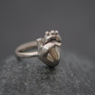 18k white gold anatomical heart set with tiny diamonds on simple ring band