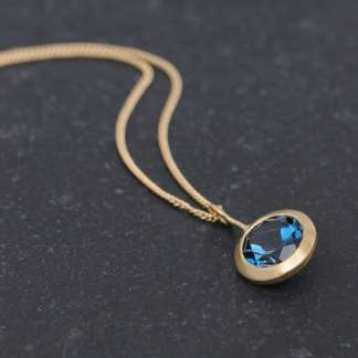 Bright London blue topaz pendant, set in recycled gold on a gold chain. This 18k yellow gold necklace is designed and handmade by William White in Cornwall