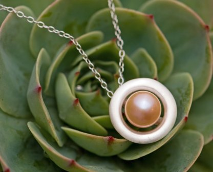 Very pretty peach freshwater pearl set in a halo pendant of satin finished sterling silver. Designed and handmade by William White in Cornwall, UK