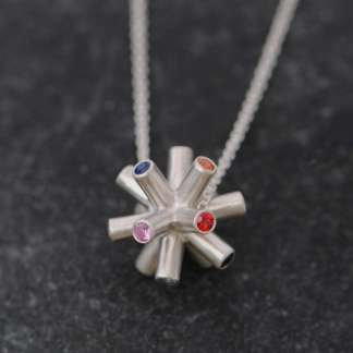 This unique pendant necklace in silver is set with 14 blue, pink, orange, red and green sapphires. Designed and handmade by William White inspired by CERN