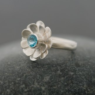 Bright blue Swiss blue topaz stone set in silver daisy ring