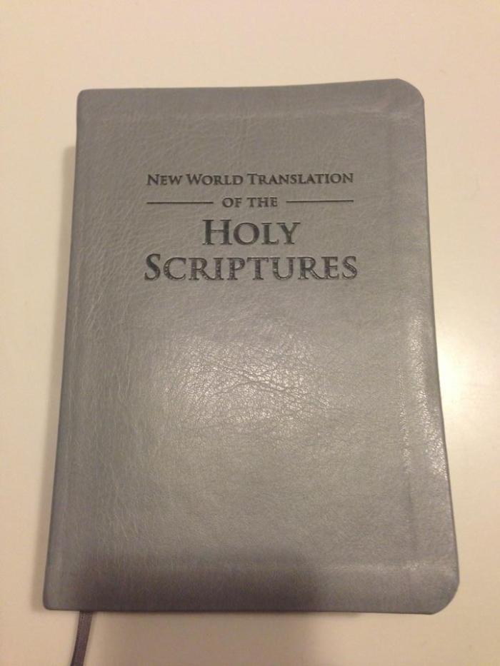 A Revisão da Tradução do Novo Mundo das Escrituras Sagradas (em inglês) possui uma capa de couro acinzentada.
