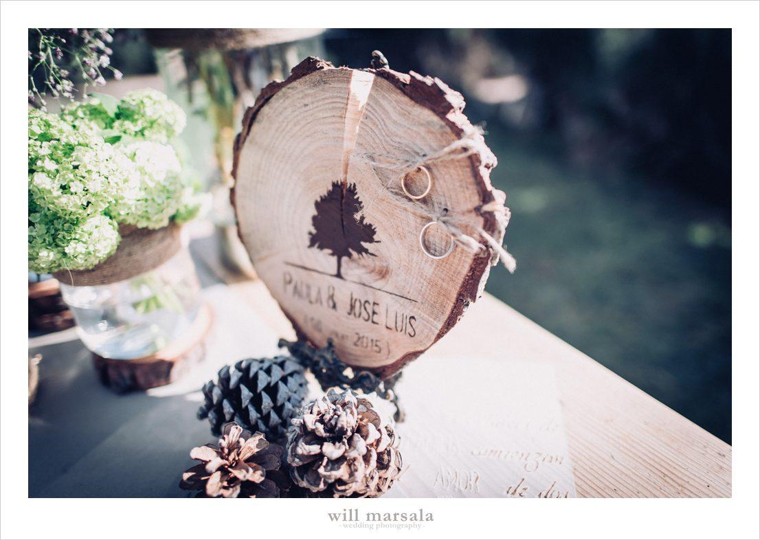detalle para llevar los anillos de boda en un tronco de madera y piñas de decoración