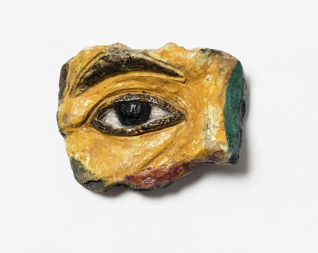 Billede af J.F. Willumsens første keramiske værk med glasur. Udsnit af et højre øje. Øje og øjenbryn er sort/mørk brunt, ansigtet i gul glasur.