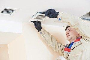 industrial builder installing ventilation or air conditioning filter holder in ceiling