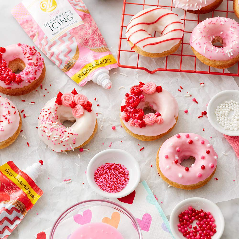 Doughnuts with pink and white icing and topped with a variety of pink, red, and white sprinkles in the process of being decorated image number 1