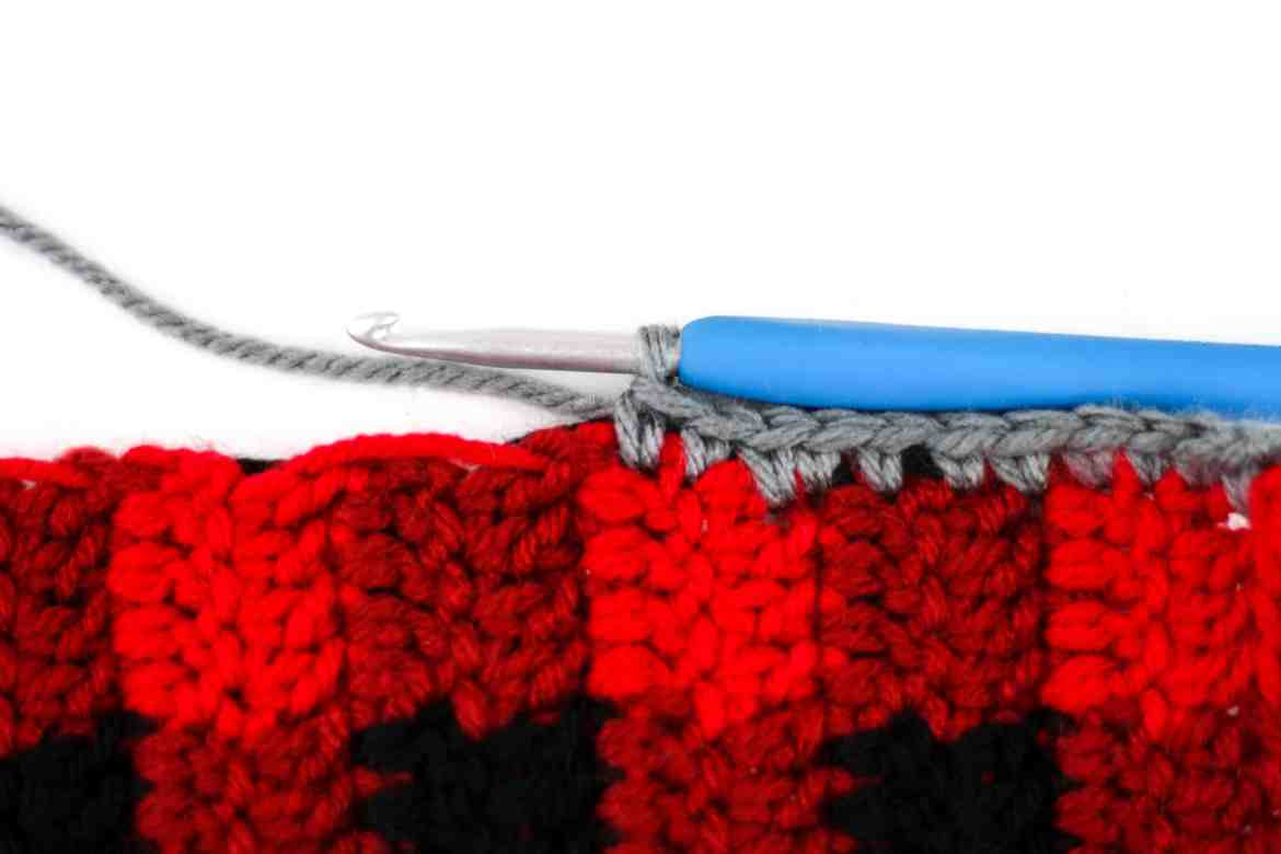 Crochet this Buttoned Plaid Cowl with this free crochet pattern. Complete with diagrams and written instructions to help make crocheting a buffalo plaid design easy even for beginners. With the textured accents and button closure this buffalo plaid crochet cowl makes a great accessory. This is a great crochet pattern for men and makes a great gift. #crochetformen