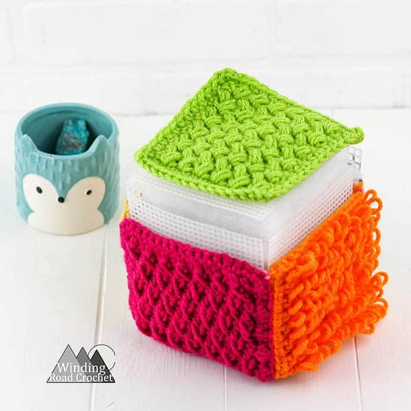 This crochet sensory block is a great toy for babies and toddlers. Learn to make one with this free crochet tutorial. #crochetforbaby #crochetbabytoy