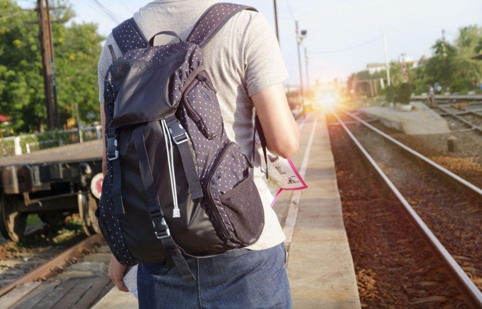 Man with rucksack on train station platform