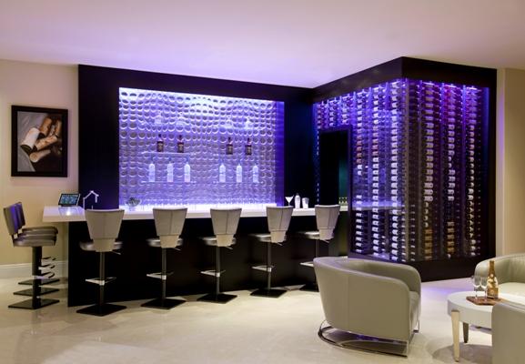 Adega da Wine Cellar Designs chamativa e luxuosa em sala de estar estilo bar com poltronas e cadeiras  brancas