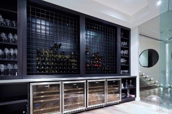 Espaço com quatro  adegas climatizadas mais suporte metálico preto para guardar garrafas e armário no mesmo tom para taças de vinho