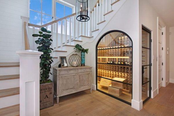 Ambiente com escada branca aproveitando o espaço abaixo da escada para uma adega clássica, com luzes amarelas. Projeto da Brandon Architects