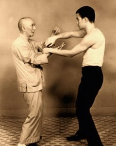 Grandmaster Ip Man practicing chi sau with a young Bruce Lee.