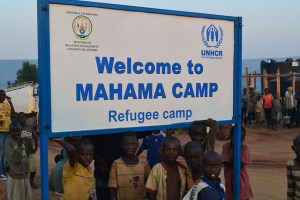 """Children standing under a large blue sign labelled """"Welcome to Mahama Camp"""""""