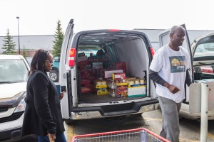 A duo loads up donations into the back of a van