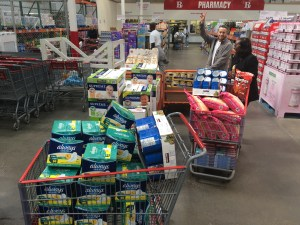 A duo pushes several shopping carts filled with a large amount of donated goods through a Costco