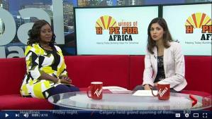 Aline being interviewed on Global News while sitting on a red couch with the interviewer