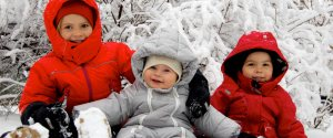3 young children dressed in heavy winter jackets outside in the snow
