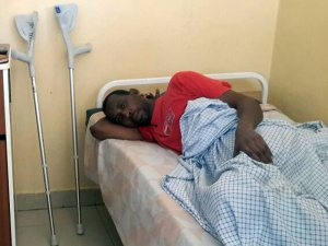 A man lays in bed with crutches beside him