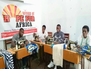 A group of 4 people working on sewing machines