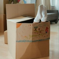 Child's feet sticking out of moving box
