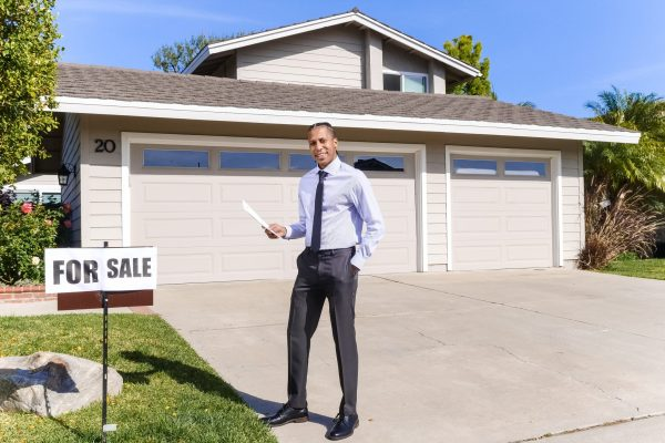 Real estate agent in front of house
