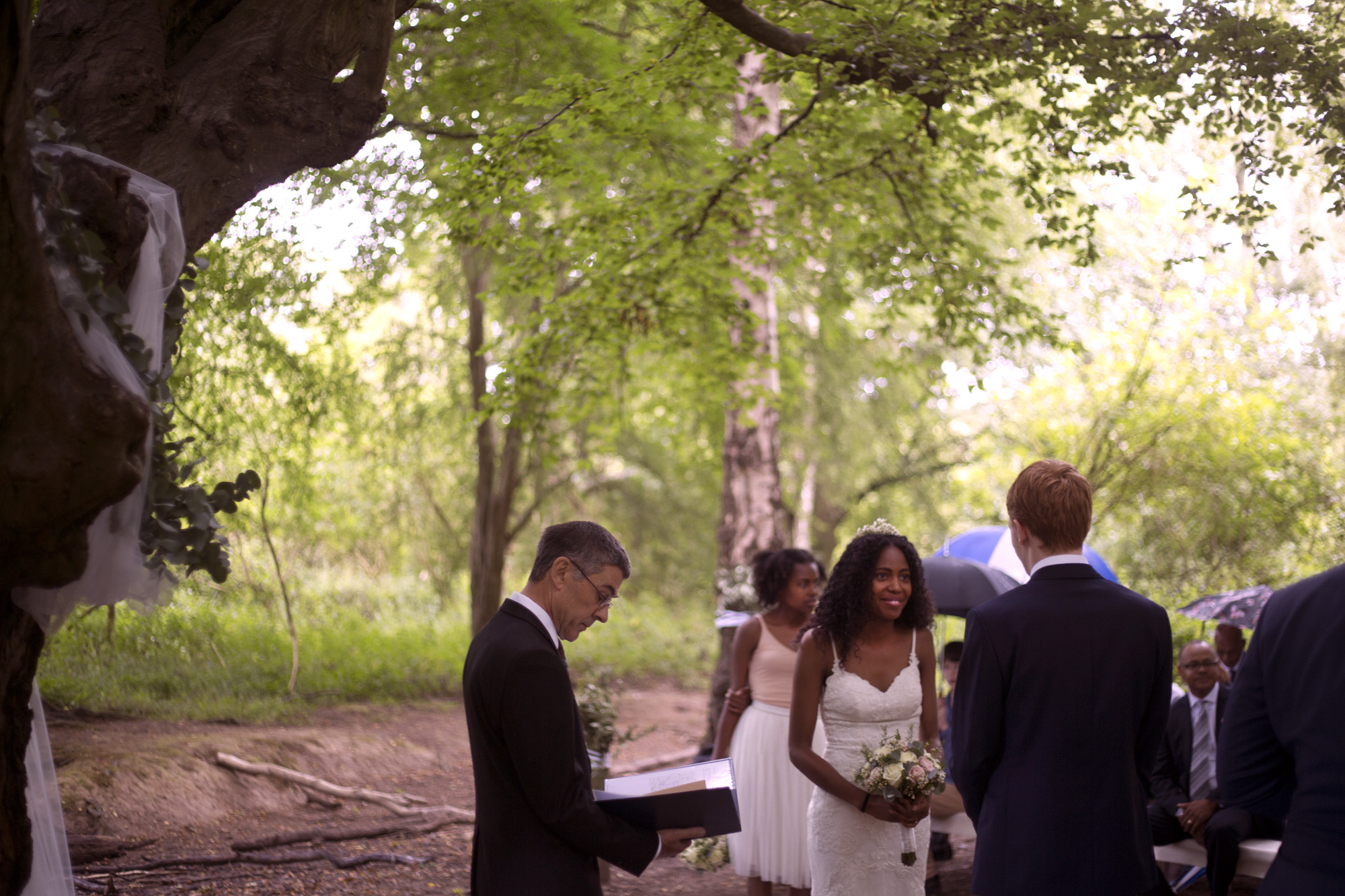 Minister leads ceremony while bride and groom smile at each other woodland wedding photographer
