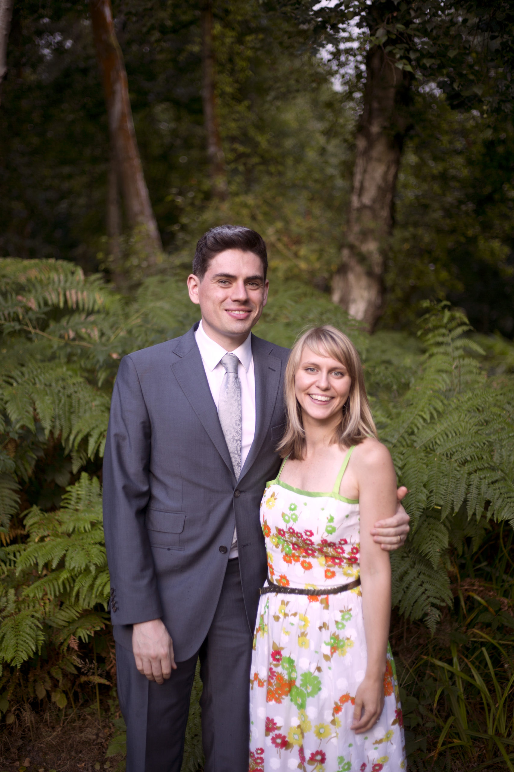 Wedding guests smile in front of ferns at Cuffley camp outdoor woodland wedding photographer